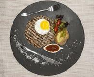 大水多的烤牛排使有大理石花纹的牛肉用鸡蛋烘烤了土豆用烤肉汁 服务在有叉子和匙子的一块石板材  库存照片