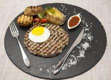 大水多的烤牛排使有大理石花纹的牛肉用鸡蛋烘烤了土豆用烤肉汁 服务在有叉子和匙子的一块石板材  免版税图库摄影