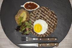 大水多的烤牛排使有大理石花纹的牛肉用鸡蛋烘烤了土豆用烤肉汁 服务在有叉子和匙子的一块石板材  库存图片