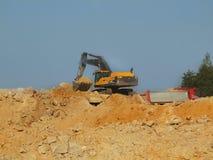 大黑橙色挖掘者在开放沙子矿等待新的转移 库存照片