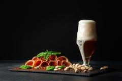 大玻璃充分与泡沫、可口熏火腿和菠菜的低度黄啤酒在黑背景 在附近的开心果 免版税库存图片