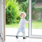 大玻璃门的可爱的卷曲女婴对庭院 免版税库存照片