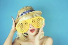 戴大滑稽的眼镜的愉快的淘气金发妇女 库存照片