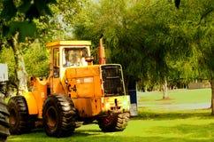 大黄色推土机在绿草,非常好的颜色constrasts停放了 库存照片