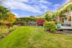 大绿色操刀了有秋天甲板的风景和看法的后院 免版税库存图片