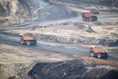 大黄色矿用汽车和推土机在工作产业站点 免版税库存图片