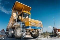 大黄色矿用汽车车,卡车卸载被开采的矿石或白垩或者石灰石 采矿业概念 免版税库存图片