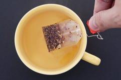 大黄色茶杯子用手 库存图片