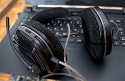 黑大dj耳机在膝上型计算机离开在混合的音乐以后 免版税库存图片