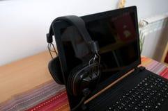 黑大dj耳机在膝上型计算机离开在混合的音乐以后 免版税图库摄影