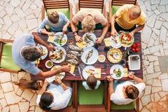 大miltigeneration家庭晚餐在过程中 在桌上的顶视图垂直的图象用食物和手 免版税图库摄影