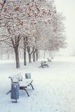 天与长凳的冬天风景在城市公园胡同  免版税图库摄影