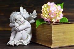 天使、花和闭合的书籍 免版税库存图片