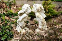 天使两个雕象在庭院里 免版税库存照片