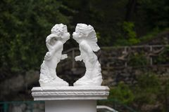 天使亲吻雕象在绿色叶子的 免版税库存照片