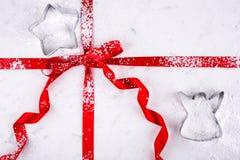 天使和星在红色丝带包裹的大理石酥皮点心板的曲奇饼切削刀拂去了灰尘用糖果商糖 免版税库存图片