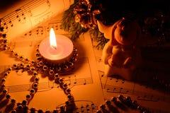 天使圣诞节装饰、蜡烛、形象和笔记 免版税库存照片