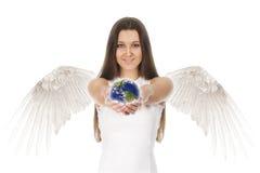 年轻天使妇女在手上的拿着地球在白色后面 图库摄影