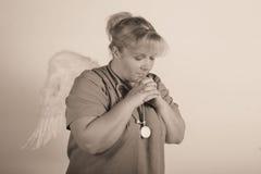 天使护士祈祷 免版税库存照片