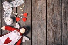 天使有心脏、鞋带丝带、按钮和三红色心脏的一个软的玩具在老木背景 在红色玫瑰色华伦泰白色的概念重点 顶层 免版税库存图片