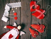 天使有心脏、鞋带丝带、按钮和三红色心脏的一个软的玩具在老木背景 在红色玫瑰色华伦泰白色的概念重点 顶层 图库摄影