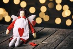 天使有心脏的一个软的玩具坐老木背景 在红色玫瑰色华伦泰白色的概念重点 选择聚焦 免版税库存照片