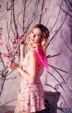 天使服装的年轻美丽的妇女有桃红色翼的 免版税库存图片