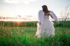 天使的图象的一个少妇在小山站立用被举的手 库存图片