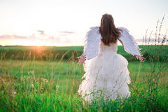 天使的图象的一个少妇在小山站立用被举的手 免版税库存图片