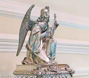 天使的小雕象和其他减速火箭的事在一张木桌上站立 免版税库存照片