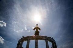 天使的雕象和在它上的太阳 免版税库存图片