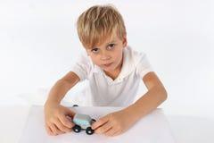 天使看的男孩显示他喜爱的木汽车玩具并且要使用 免版税图库摄影