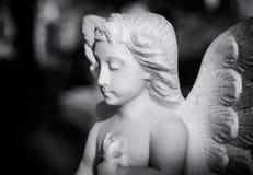 年轻天使雕象在伦敦公墓看下来,当祈祷时 库存图片