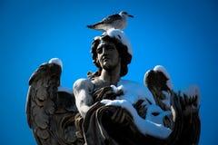 天使雕象在罗马-意大利-在与雪的冬天 免版税库存图片
