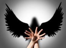 天使,手阴影喜欢黑暗翼  免版税库存照片