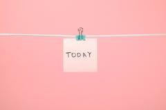 今天垂悬在与文本的串的桃红色纸笔记 库存图片