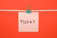 今天垂悬在与文本的串的桃红色纸笔记 库存照片
