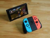 任天堂开关,在木桌上的电子游戏控制台 免版税图库摄影