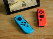 任天堂开关,在木桌上的电子游戏控制台 免版税库存照片