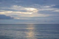 天堂般的天空和风平浪静在黎明 免版税库存照片