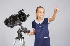 年轻天文学家显示满天星斗的天空,当站立在望远镜时 免版税库存图片