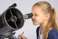 年轻天文学家通过望远镜和纪录结果的目镜看 免版税库存照片