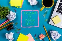今天是您的天 办公室有供应的桌书桌,白色空白的笔记本,杯子,笔,个人计算机,弄皱了纸,在蓝色的花 库存照片