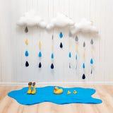 天气符号 手工制造室装饰覆盖与雨下落、水坑、儿童黄色胶靴、伞和鸭子 免版税库存图片