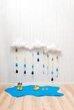 天气符号 手工制造室装饰覆盖与雨下落、水坑、儿童黄色胶靴和鸭子 库存照片