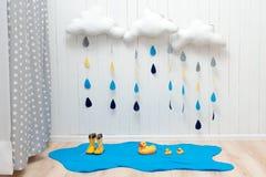 天气符号 手工制造室装饰覆盖与雨下落、水坑、儿童黄色胶靴和鸭子 免版税库存图片