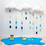 天气符号 手工制造室装饰覆盖与雨下落、水坑、儿童黄色胶靴和鸭子 免版税库存照片