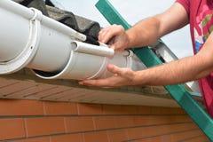 天沟管道设施 盖屋顶的人承包商安装和修理雨天沟 Guttering修理 图库摄影