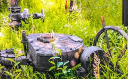 天然气的发行的老金属机制在草丛林的  免版税图库摄影