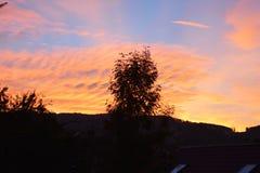 天的美妙的结尾 在山土坎的日落 与明亮的红色血液颜色的美好的风景 库存照片